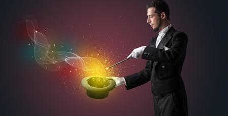 Illusionist hand starts to conjure with white glove and magic wand Standard-Bild - 119414606