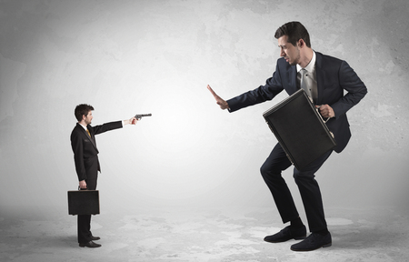 Tiny businessman with gun shooting giant fearful businessman