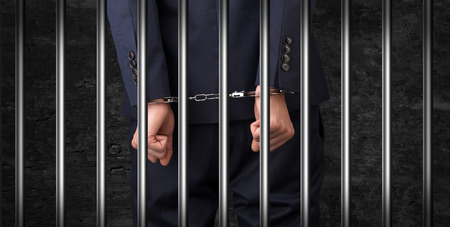 Close convicted man with handcuffs behind grids Standard-Bild - 119414864