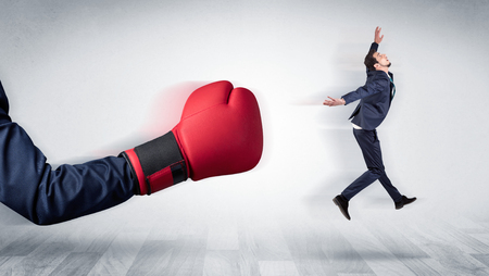 Big red boxing glove knocks out little businessman concept