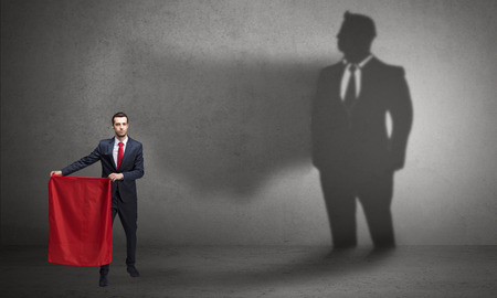Businessman standing with red cloth on his hand and his shadow on the background