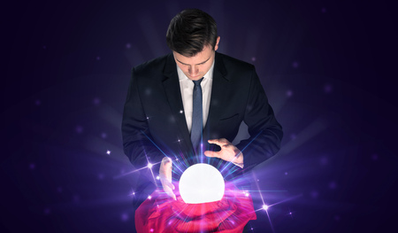 Young businessman sitting with crystal ball in action Archivio Fotografico