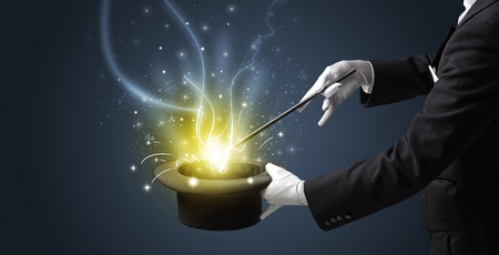 Magician hand conjure with wand  light from a black cylinder Standard-Bild - 119415671