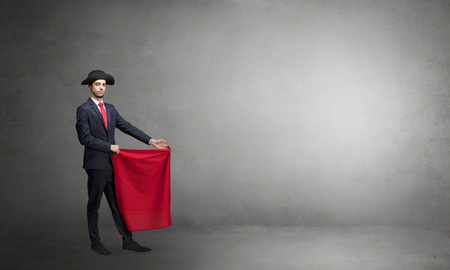 Businessman standing with red toreador cloth in his hand in an empty room Reklamní fotografie