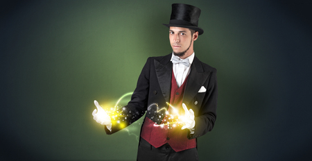 Magician holding his sparkling power between his two hand Standard-Bild - 119417081