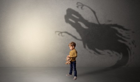 Scary ghost shadow in a dark empty room with a cute blond child Stock Photo