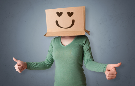 Funny woman wearing cardboard box on her head with smiley face Stock Photo