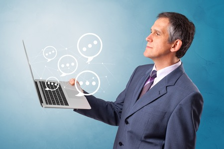 Man holding laptop with a few speech bubble symbols
