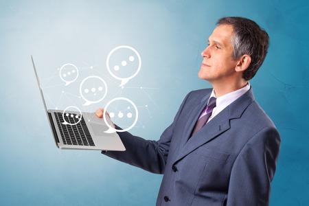 Man holding laptop with a few speech bubble symbols Reklamní fotografie - 120333399