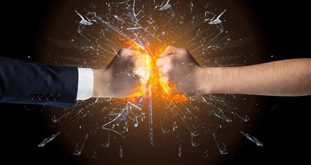Two hands fighting and breaking a glass into small pieces