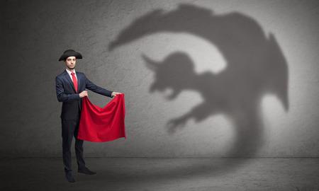 Geschäftsmann, der mit rotem Tuch in der Hand und Koboldschatten auf dem Hintergrund steht Standard-Bild
