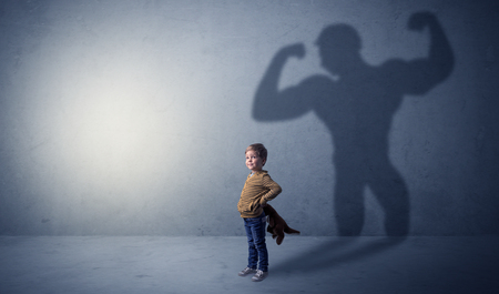 Little waggish boy in an empty room with musclemen shadow behind Stock fotó