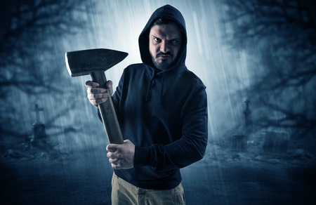 Armed aggressive hunter in abandoned thick forest graveyard concept Stock Photo