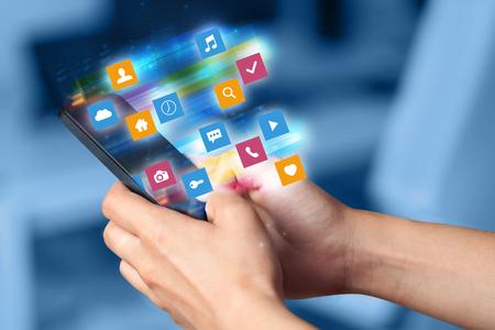 カラフルな高速動くアプリケーションアイコンとシンボルの概念と携帯電話を使用して手