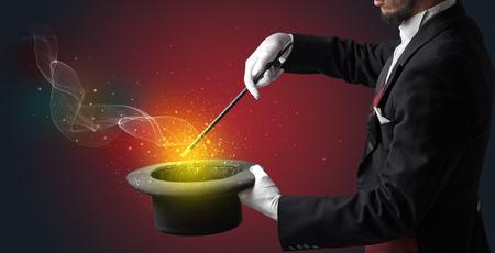Illusionist hand starts to conjure with white glove and magic wand Standard-Bild - 120332608