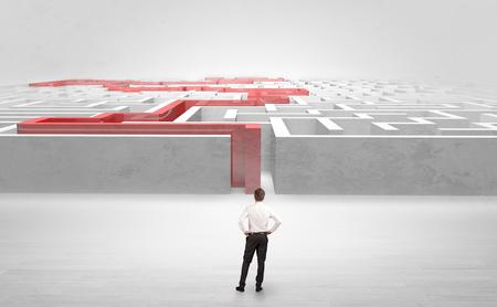 Homme d'affaires se préparant à entrer dans le labyrinthe avec le concept de route indiqué