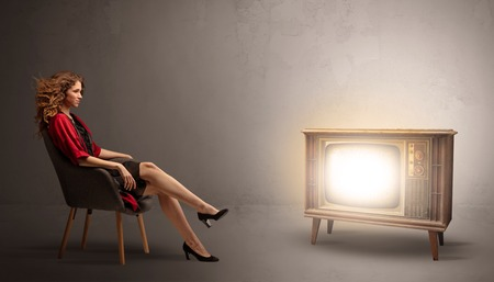 Elegant young lady watching to a vintage television