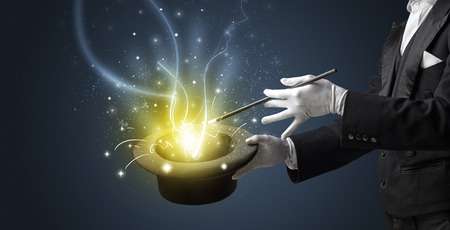 Magician hand conjure with wand  light from a black cylinder Standard-Bild - 120331984