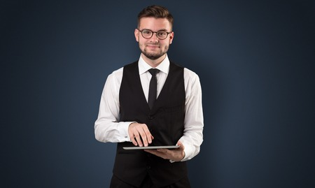 Handsome spectacled businessman holding a tablet with dark background 版權商用圖片