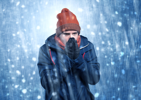 Handsome young boy shivering and trembling at snowstorm concept Stock Photo