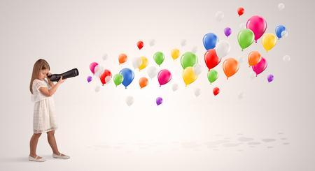 Cute girl looking to air balloons through a telescope