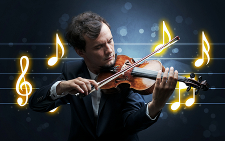 Young handsome fiddler playing with music sheet background