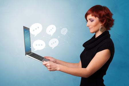 Woman holding laptop with a few speech bubble symbols Reklamní fotografie - 121099628