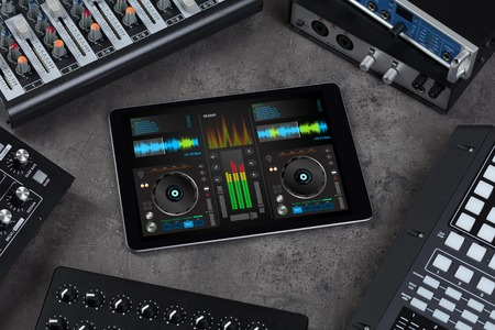 Mixing music on tablet with electronic music instruments concept 写真素材 - 121099630