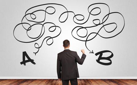 El empresario busca la conexión entre dos cosas mientras está de pie frente a una pared