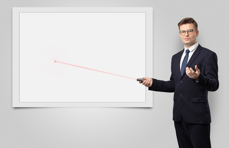 Young businessman with laser pointer and copyspace white blackboard