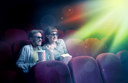 Teenager couple cuddling and watching the climax part of the movie Stock Photo