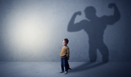 Little waggish boy in an empty room with musclemen shadow behind Stock Photo