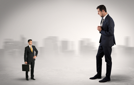 Giant businessman being afraid of small serious executor with suitcase Stock fotó - 121099837
