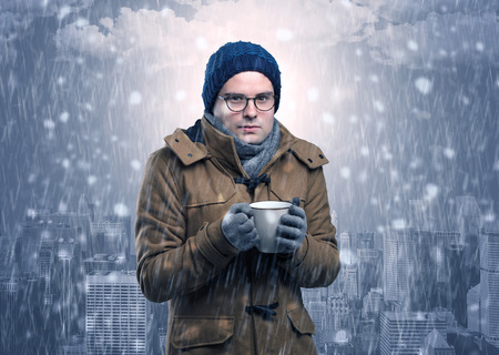 Young man freezing in warm clothing with city concept Stock Photo