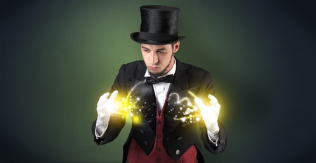 Magician holding his sparkling power between his two hand Standard-Bild - 120952490