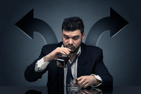 Drunk disappointed man sitting at table with arrows around