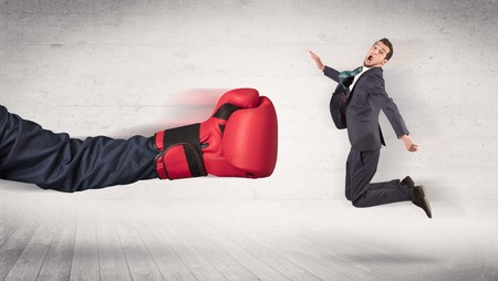 Arm with red boxing gloves hits office worker concept Standard-Bild