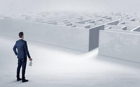 Geschäftsmann, der sich bereit macht, das Labyrinth mit Objekten in seinem Handkonzept zu betreten