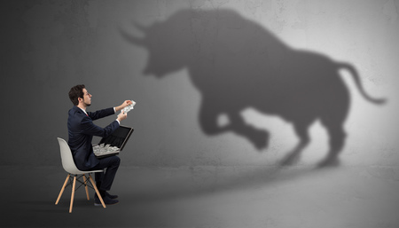 Humble businessman staying and offering stuffs to a huge angry bull shadow