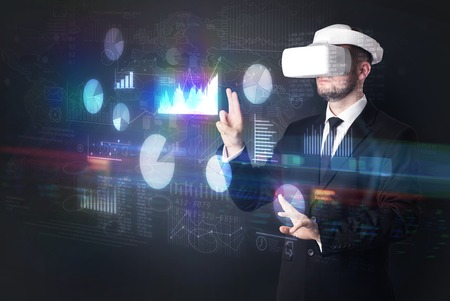 Elegant businessman in DJI goggles handling 3D reports and charts around him