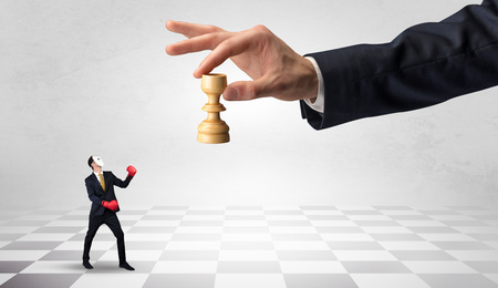 Small businessman fighting against big chessman on a big hand with chess board concept Фото со стока - 120806529