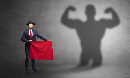 Businessman standing with red cloth on his hand and strong hero shadow on the background