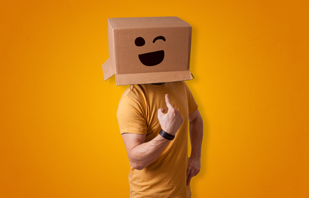 Funny man wearing cardboard box on his head with smiley face Foto de archivo