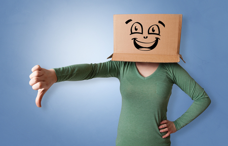 Young woman with happy face illustrated cardboard box on her head Foto de archivo