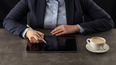 Business woman working on  tablet with dark background and copyspace 스톡 콘텐츠