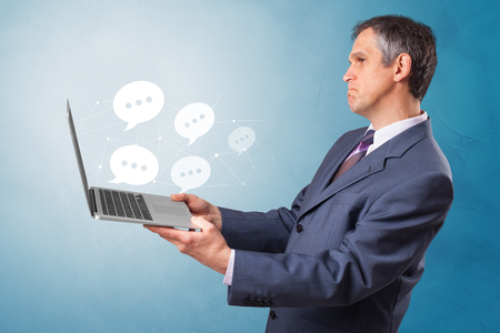 Man holding laptop with a few speech bubble symbols Reklamní fotografie - 121157673
