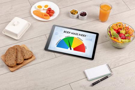 Comida sana con tableta sobre un fondo de madera con palabras índice de masa corporal. Concepto de salud. Foto de archivo