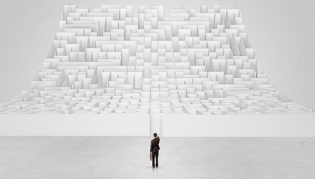 Businessman standing and thinking in front of a curved infinity maze Stockfoto