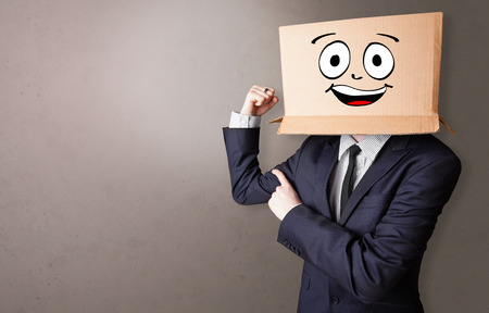 Young boy standing and gesturing with a cardboard box on his head Stock Photo