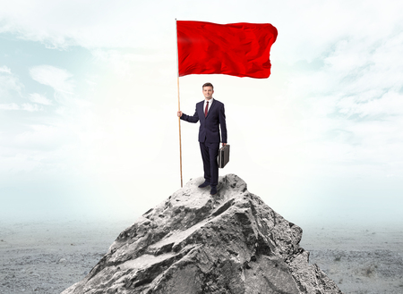Handsome businessman on the top of the mountain with red flag